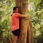 Jeune femme faisant un câlin à un arbre. Plan large