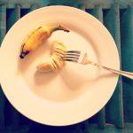 Banane écrasée à la fourchette et assiette blanche